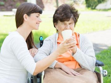 Jüngere Frau hilft älteren Frau im Rollstuhl beim trinken