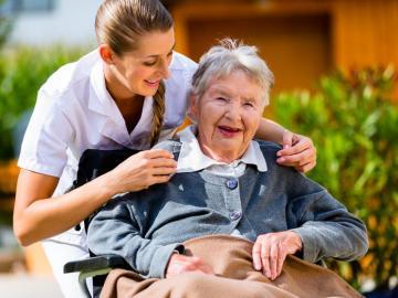 Junge Frau lehnt sich über ältere Frau im Rollstuhl