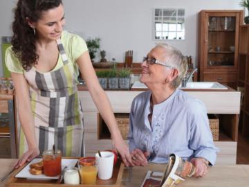 Betreuerin stellt einer alten Dame ein Frühstückstablett auf den Tisch.