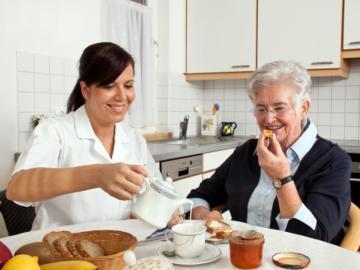 Pflegerin unterstützt eine ältere Dame beim Frühstück