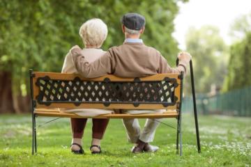 Ein älteres Paar sitzt auf einer Parkbank.
