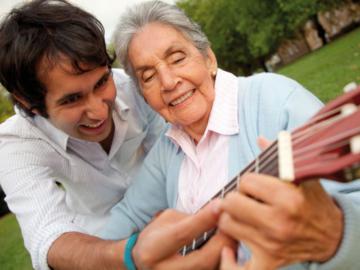 Ein junger Mann unterstützt eine ältere Frau beim Gitarre spielen.