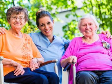 Zwei ältere Frauen sitzen im Rollstuhl,  zwischen ihnen kniet eine Pflegerin.