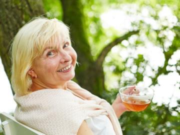 Eine ältere Dame sitzt auf einer Bank neben einem Baum und trinkt Tee.