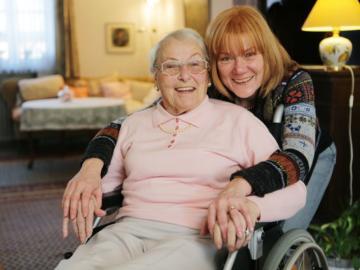 Eine jüngere Frau beugt sich über eine ältere Frau, die im Rollstuhl sitzt.