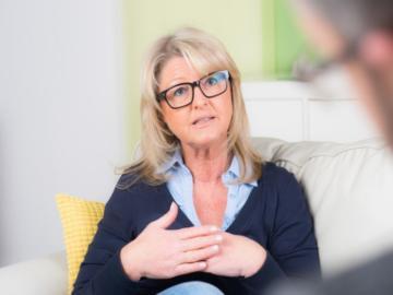 Eine Frau sitzt einem Herrn mit Brille gegenüber.
