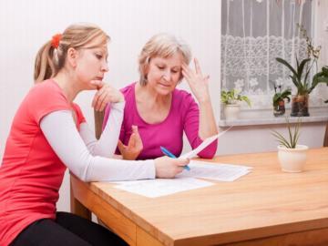 Zwei Frauen sitzen an einem Tisch und halten Zettel in der Hand.