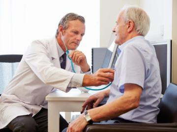 Ein Arzt hört mit einem Stethoskop die Brust eines älteren Herrn ab.