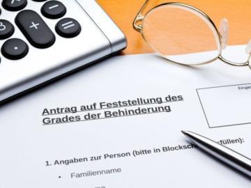 Ein Antragsformular auf dem ein Stift und eine Brille liegen.