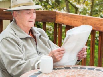 Ein älteree Herr liest eine Zeitung am Balkon.