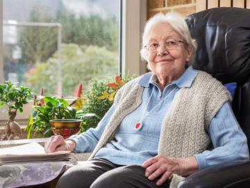 Eine ältere Dame sitzt in einem Stuhl.