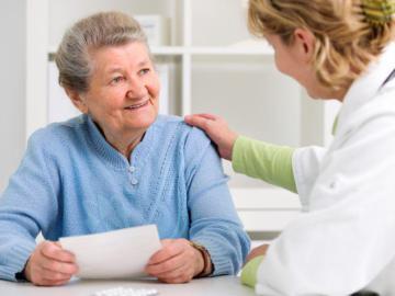 Eine Ärztin greift einer älteren Dame auf die Schulter.