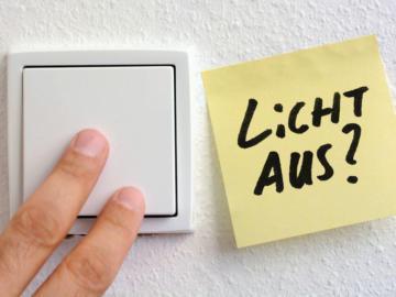 """Ein Lichtschalter wird gezeigt, daneben hängt ein Post-it auf dem steht """"Licht aus?"""""""