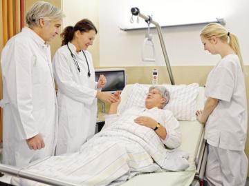 Drei MitarbeiterInnen in einem Krankenhaus stehen neben einem Krankenbett, in dem eine ältere Dame liegt.