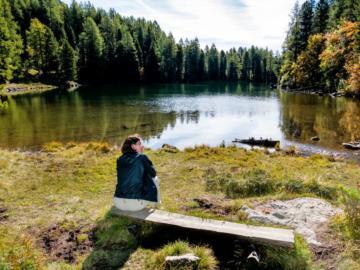 Eine Frau sitzt auf einer Bank vor einem See.