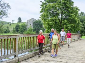 Eine Wandergruppe überquert eine Holzbrücke.