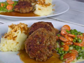 Foto eines Tellers mit Fleischlaibchen mit Gemüse und Pürree.