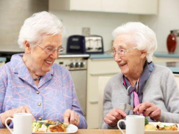 Zwei ältere Damen sitzen lachend beim Mittagessen am Tisch.