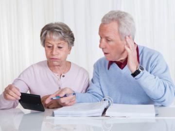 Ein älteres Paar sitzt vor einem Aktenordner mit einem Taschenrechner in der Hand.
