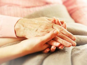 Eine ältere Hand, die in der Hand einer jüngeren Frau liegt.