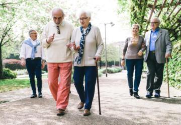 Zwei ältere Paare und ein Herr spazieren.