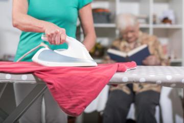 Eine Frau bügelt Wäsche, im Hintergrund sitzt eine ältere Dame die liest.