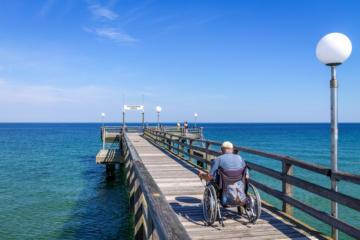 Ein älterer Herr im Rollstuhl steht auf einem Steg, der ins Meer führt.