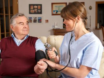 Pflegerin misst Blutdruck bei älterem Herrn