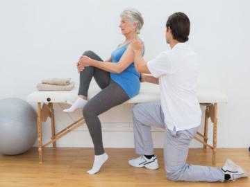 Eine älterr Frau erhält eine Rückenbehandlung.