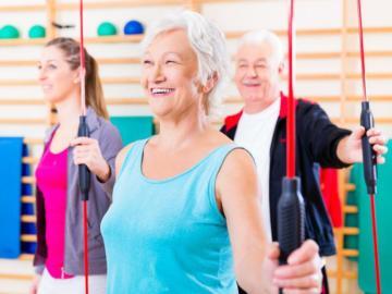 Eine ältere Frau im Turnsaal mit Trainingsgerät.