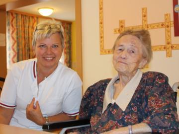 Eine Pflegerin sitzt neben einer alten Frau im Rollstuhl.