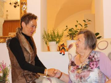 Eine Frau reicht einer älteren Frau die Hand.