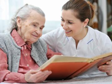 Ältere und Jüngere Frau schauen sich gemeinsam ein Buch an