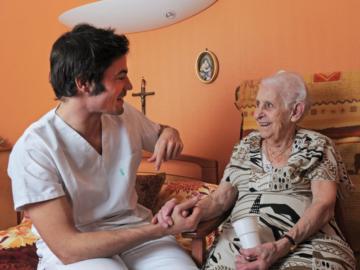 Pfleger hält einer alten Dame die Hand