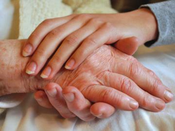 Hände einer jüngeren Frau umfassen die Hände einer älteren Frau.