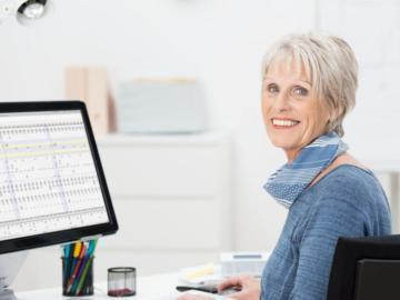 Eine ältere Dame sitzt vor einem Computer.