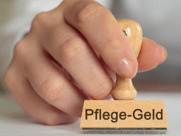 """Ein Stempel mit der Aufschrift """"Pflegegeld""""."""