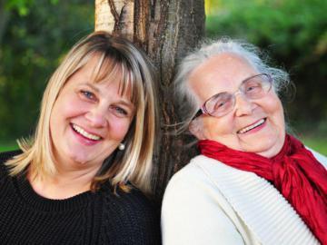 Eine jüngere und eine ältere Frau, die an einem Baum lehnen.