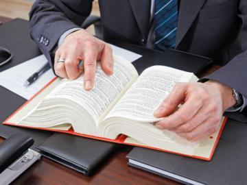 Eine Person blättert in einem Rechtsbuch.