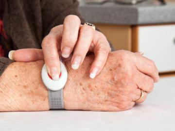 Hände einer älteren Frau, die eine Notrufuhr trägt