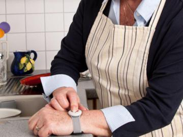 Handgelenk einer älteren Frau, die eine Notrufuhr trägt und den Notrufknopf drückt.