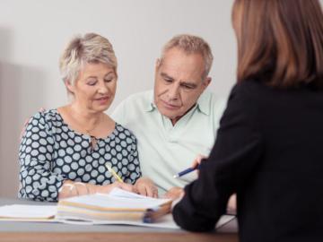 Ein älteres Paar sitzt einer Dame gegenüber,  die auf einen Aktenordner zeigt.