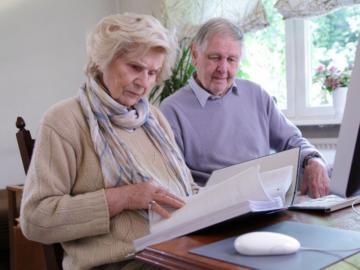 Ein älteres Paar sitzt vor einem Computer und blättert in einem Aktenordner.