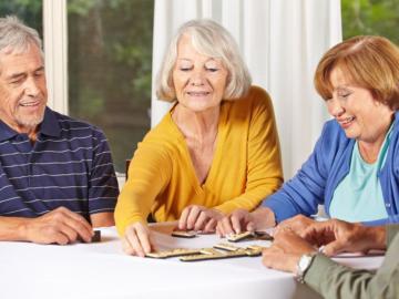 Zwei ältere Frauen und ein älterer Herr sitzen am Tisch und spielen ein Spiel.