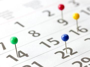 Kalenderblatt auf dem Stecknadeln gesetzt sind.