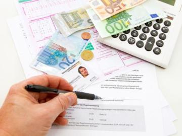 Ein Tisch auf dem Geldscheine und ein Taschenrechner liegen und eine Hand die einen Stift hält.