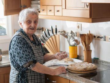 Eine ältere Frau mit Kochschürze steht vor einem Kuchenteller.