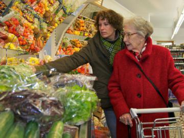 Eine jüngere Frau steht hinter einer älteren Frau mit einem Einkaufswagen.