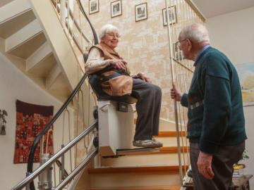 Ältere Frau sitzt auf einem Treppenlift, ein älterer Herr schaut ihr zu